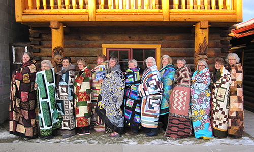 Bear's Paw Quilt staffers  wrapped in their quilts